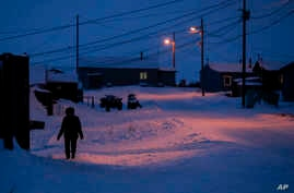 FILE - In this Jan. 20, 2020, file photo, a woman walks before dawn in Toksook Bay, Alaska, a mostly Yup'ik village on the edge…