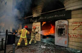 Firefighters extinguish a fire at a branch of the Credit Libanais Bank that was burnt by anti-government protesters, in the northern city of Tripoli, Lebanon, Tuesday, April 28, 2020.