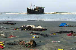 Belongings of Rohingya refugees lay on the shore as their carrier boat remains anchored nearby in Teknaf, Bangladesh. Thirty-two Rohingya died on an overcrowded fishing trawler stranded in the Bay of Bengal for nearly two months, officials said.