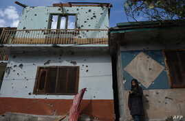 FILE - A Kashmiri girl stands in front of her damaged family house after cross-border shelling in Jura, a village of Neelum valley in Pakistan-administered Kashmir, Oct. 22, 2019.