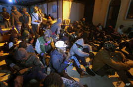 FILE - Migrants sit on the floor at a detention center inTajoura, in the eastern suburbs of the Libyan capital Tripoli, Nov. 29, 2019.