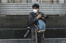 FILE - AFP photographer Alfredo Estrella wears a face mask as he works during the coronavirus pandemic, in Mexico City, Mexico, April 8, 2020.