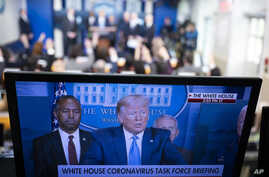 FILE - A TV screen shows President Donald Trump speaking on the coronavirus outbreak, at the White House, March 21, 2020, in Washington. A lawsuit in Wisconsin is blocking a local TV station from airing an ad blasting Trump's response to the crisis.