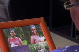 In this image taken from video, Margaret Ntale, whose three student daughters are stranded in Wuhan, looks at photographs of her children as she speaks to The Associated Press at her house in Kampala, Uganda, Feb. 27, 2020.