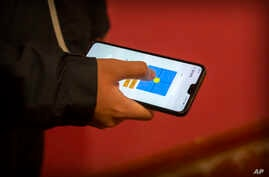 FILE - A person uses a smartphone app in Beijing, China, March 18, 2020.