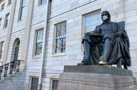 FILE - The John Harvard statue at Harvard University, a popular tourist attraction at the campus in Cambridge, Masssachusetts, sits adorned with a protective mask, March 14, 2020.