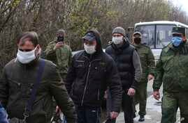 Ukrainian war prisoners, escorted by Russia-backed separatist soldiers, all wearing face masks to protect against coronavirus, walk to be exchanged near a checkpoint in Horlivka, eastern Ukraine, April 16, 2020.