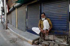 FILE - An Indian Muslim sits in front of closed shops during a coronavirus shutdown in Prayagraj, India, April 5, 2020.