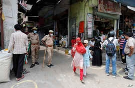 Policemen stand guard as people shop during a limited opening of small grocery stores amid the coronavirus pandemic, in Prayagraj, India, April 25, 2020.