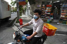 Grocery delivery man Saeed Vatanparast, wearing a face mask to protect against the coronavirus, leaves on his motorcycle for a delivery, in Tehran, Iran, April 21, 2020.