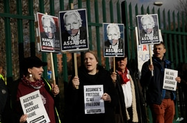 Supporters of Julian Assange hold placards as they protest on the second day of a week of opening arguments for the extradition of Wikileaks founder Julian Assange outside Belmarsh Magistrates' Court in south east London, Feb. 25, 2020.