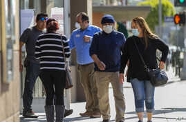 Customers, wearing masks, wait their turn to enter a bank in Los Angeles, Califiornia, April 3, 2020.