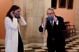 Dr. Amy Acton, left, director of the Ohio Department of Health, and Ohio Gov. Mike DeWine put on their homemade masks following a news conference on the state's response to the ongoing COVID-19 pandemic, April 6, 2020, at the Ohio Statehouse in Columbus.