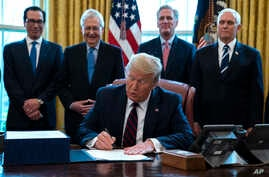 President Donald Trump signs the coronavirus stimulus relief package in the Oval Office at the White House in Washington, March 27, 2020.