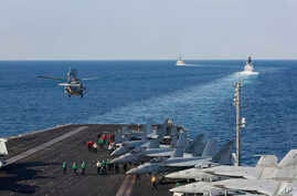 FILE - In this Nov. 19, 2019, photo, made available by the U.S. Navy, a helicopter lifts off from the aircraft carrier USS Abraham Lincoln as it transits the Strait of Hormuz.