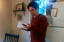 In this March 25, 2020 image taken from video by Caillin Wells, neuroscientist Michael Wells works on the COVID-19 Pandemic Shareable Scientist Response Database in his home in Cambridge, Massachusetts.