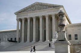 People walk outside the Supreme Court in Washington, March 16, 2020.