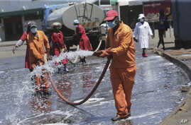 Harare City Council workers disinfect a bus terminal, in Harare, Zimbabwe, April, 1, 2020.