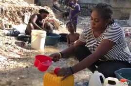 A woman mixes Clorox with water to drink  in Port-au-Prince, Haiti, on April 3, 2020. Some Haitians believe the mixture can prev