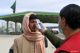 FILE - A health worker takes the temperature of a Afghan national at the Chaman crossing point on the Pakistan-Afghanistan border, in Chaman, Pakistan, Feb. 26, 2020.