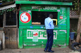 FILE - A customer conducts a transaction at a mobile money transfer stall in Nairobi, Kenya, Oct. 16, 2018. Due to the coronavirus crisis, millions of Africans rely on remittances more so than ever.