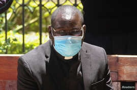 Kenyan Catholic priest Richard Onyango Oduor sits on an open-air dock as he was charged at the Milimani Law Courts with spreading the coronavirus, in Nairobi, Kenya, April 16, 2020.