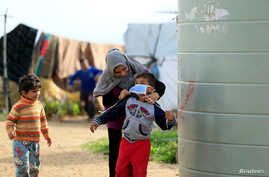 A Syrian refugee woman puts a face mask on a boy as a precaution against the spread of coronavirus, in al-Wazzani area, in southern Lebanon, March 14, 2020.