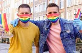 Gay couple Dawid Mycek and Jakub Kwiecinski pose with the rainbow-patterned face masks on a street in Gdansk, Poland, April 8, 2020.