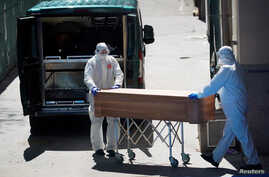 Mortuary workers push a coffin of a person who died at a nursing home during the coronavirus disease (COVID-19) outbreak in Leganes Madrid, Spain, April 2, 2020.