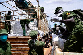 Members of Local Defense Unit (LDU) unload relief food to civilians who are affected by the lockdown to prevent the potential spread of coronavirus, in Kampala, Uganda, April 4, 2020.