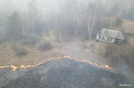 An aerial view shows grass and plants on fire, as an operation to extinguish wildfires around the defunct Chernobyl nuclear plant continues, in Lyudvynivka in Kyiv Region, Ukraine, April 18, 2020.