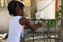 A young girls washes her hands at the electric water bucket invented by Haitian teen, Wens Dimanche in the Delmas neighborhood of Port-au-Prince, Haiti. (Photo: Matiado Vilme / VOA)