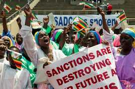 Demonstrators hold placards as they chant slogans and wave Zimbabwe's national flags during a rally to denounce US and EU…
