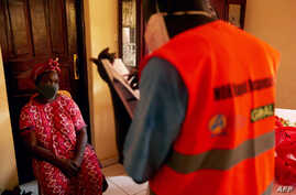 A member of the South Sudanese Ministry of Health Rapid Response Team questions to a woman for testing at her home as she…