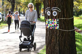 A woman pushes a pram past a giant mask and eye display stuck to a tree in Melbourne on May 8, 2020, as Australia's government…