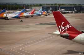 Virgin Atlantic, TUI, and Jet2 operated aircraft stand on the apron the departure gates at Manchester Airport in Manchester,…