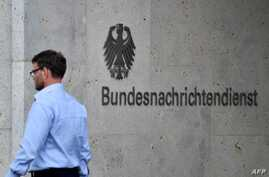 A picture taken on May 19, 2020 shows an employee walking past the name of German Federal Intelligence Service (BND) at its…