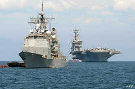 The US aircraft carrier Carl Vinson (R) and the cruiser USS Bunker Hill (L) sit anchored off Manila Bay after arriving on May…