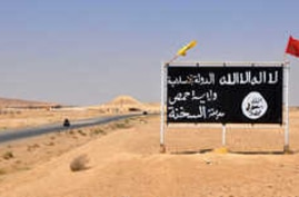 A general view taken on August 13, 2017 shows an Islamic State (IS) group poster in the central Syrian town of Al-Sukhnah on…