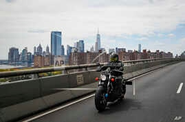 Ashley Zeolla rides her motorcycle over the Williamsburg Bridge on a delivery run of personal protective equipment to a doctors…