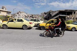Men ride a motorbike past cars, in line at a gasoline station, waiting to fuel up in Aleppo, Syria April 11, 2019. Picture…