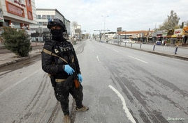 A security man stands in an empty street during a curfew imposed by Iraqi Kurdish authorities, following the outbreak of…
