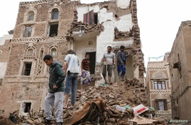 People stand on the debris of a house that recently collapsed due to heavy rains in the old quarter of Sanaa, Yemen May 3, 2020.