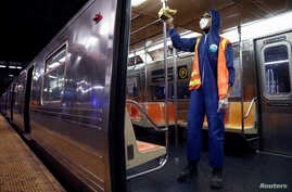 A worker wipes down surfaces as the MTA Subway closed overnight for cleaning and disinfecting during the outbreak of the…