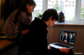 Noah aged 10 and Milly aged 7 watch Britain's Prime Minister Boris Johnson on a laptop during a broadcast to outline plans for gradually easing lockdown measures following the outbreak of the coronavirus disease (COVID-19), Hertford, Britain, May 10, 2020.