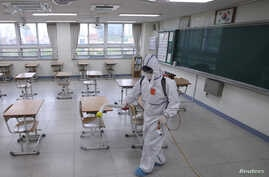 A quarantine worker sprays disinfectant at a high school, following the coronavirus disease (COVID-19) outbreak, in Seoul,…