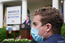 A Trump administration staffer wears a protective face mask in the Rose Garden as U.S. President Donald Trump holds a…