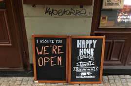 FILE PHOTO: A sign assures people that the bar is open during the coronavirus outbreak, outside a pub in Stockholm, Sweden…