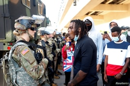 A man confronts a National Guard member guarding the area in the aftermath of a protest against death in Minneapolis
