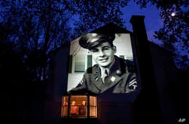 An image of veteran James Sullivan is projected onto the home of his son, Tom Sullivan, left, as he looks out a window with his…
